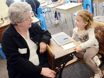Lynn Middleton-Love, a student from the late 1940's, sits in her old one-room school house class room with Jessica Geary, 3, a one-day-a-week Introduction to Junior Kindergarten student, at the 100th anniversary celebrations at Deer Park Public School in Keswick May 11.