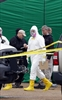 Federal authorities, some in hazmat suits, walk outside the staging area as they search at a small retail space where neighbouring business owners said Everett Dutschke used to operate a martial arts studio, on Wednesday, in Tupelo, Miss., in connection wi