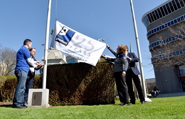 Bob Romeo, Mayor Walter Sendzik, Eleanor Lancaster and Coun. Sal Sorrento raise the Goodwill Niagara 25th anniversary flag in front of city hall on Monday.