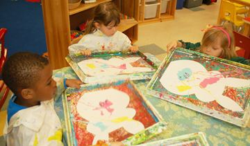 Akeem Fletcher, Amelia Cocetti and Jane Bateson don their painting smocks to create marble-swirled bunny crafts Tuesday at the Niagara Nursery School and Child Care Centre.