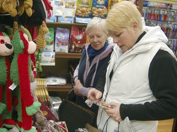 Laura Melo and Margaret Ball look at items for sale at Amelia Biscuit Company during Jingle Bell Night on Friday in downtown Paris.