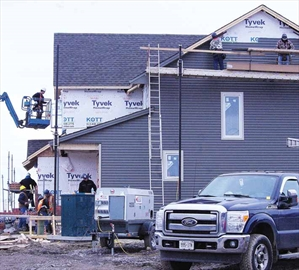 Volunteers help out Habitat for Humanity at a construction site on Cobble Hill Drive. New home construction may not be news in Barrhaven, but building a house in just 72 hours isn't the way most homes go up. For the full story, see page 20.