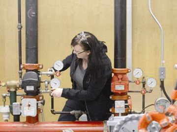 Cathie Ross practices operating the main control valves on a fire sprinkler system.