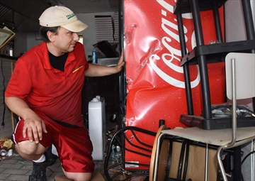 Free Topping Pizza owner Jason Rice looks at the Coca-Cola cooler, which he believes saved his life when a vehicle crashed through his storefront.