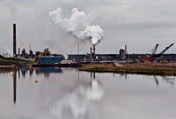 The Syncrude oil sands extraction facility is reflected in a tailings pond near the city of Fort McMurray, Alberta on June 1, 2014. Canada would have to cut its emissions almost in half over the next 12 years to meet the stiffer targets dozens of international climate change experts say is required to prevent catastrophic climate changes from the planet getting too warm. The United Nations Intergovernmental Panel on Climate Change says there will be irreversible changes and the entire loss of some ecosystems if the world doesn't take immediate and intensive action to cut greenhouse gas emissions far more than we are now. THE CANADIAN PRESS/Jason Franson