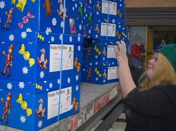 Crystal Dove, a volunteer helps unload the truck at the Brampton depot last week. The Brampton Santa Claus Fund needs delivery elves to drop-off the gift boxes to recipients.