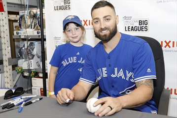 Lily Chambers, 6,  watches as Toronto Blue Jays outfielder Kevin Pillar autographs a baseball at an appearance at Home Depot on Terry Fox Way on Friday afternoon.