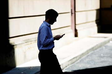 A man browses his smartphone as he walks in Philadelphia, Monday, April 8, 2019. It has become common for companies to supply smartphones or other mobile devices for their workforce — knowing full well that employees will use them both work and personal reasons. THE CANADIAN PRESS/AP Photo/Matt Rourke