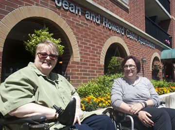 Grateful tenants Pam Read, left and Martha Johnson, right, pose in front of their homes at the Jean and Howard Caine Apartments in Oakville