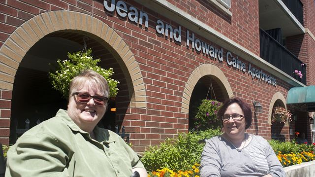 Tenants Pam Read, left and Martha Johnson, right, pose outside Jean and Howard Caine Apartments