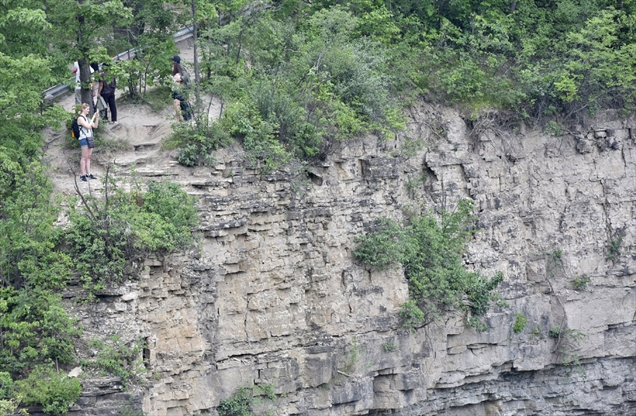 A visitor stands close to the edge opposite Albion Falls. There were 21 calls for first-responder help at local waterfalls over the last two years.