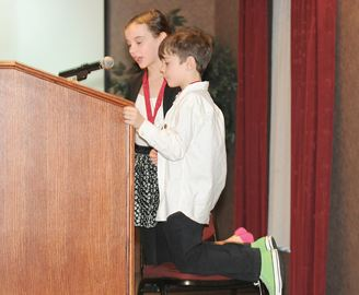 COBOURG -- YMCA Peace Medal recipients Raya, 11, and Dyan, 7, Rickerby used a chair to reach the microphone at the ceremony. The awards were presented at the Best Western on Nov. 20. November 20, 2013.