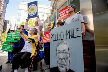 Protesters hold placards outside the County Court where Cardinal George Pell was to arrive in Melbourne, Australia, Wednesday. The most senior Catholic cleric ever convicted of child sex abuse faces his first night in custody following a sentencing hearing on Wednesday that will decide his punishment for molesting two choirboys in a Melbourne cathedral two decades ago.
