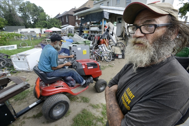 Richard Lichty manoeuvres a garden tractor in their back yard past his twin brother Steve (Pops) Hoyland. They make a living by collecting scrap metal and are spotted regularly throughout the city.