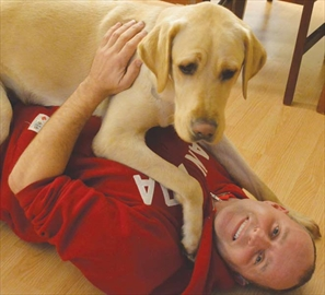 Young guide dog Lewis sits on his new owner, Kevin Frost, an Orleans resident who is visually and hearing impaired. Frost trained with his new guide dog at the Canadian Guide Dogs for the Blind headquarters in Manotick for three weeks before bringing Lewis home on Nov. 29. See story on page 6.