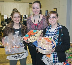 Volunteers Savanna Schnierle, Britney Goertz and Julia Gonta hold out an array of delicious treats.