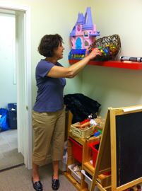 Radius Childen and Youth fundraising manager Margaret McConnell straighttens toys in a treatment room.
