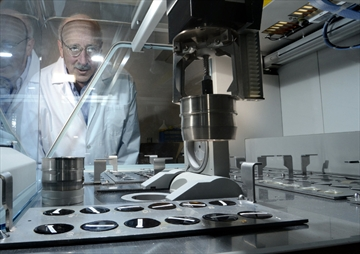 Photo of Activation Labs president Dr. Eric Hoffman watches a robotic machine analyze iron ore samples