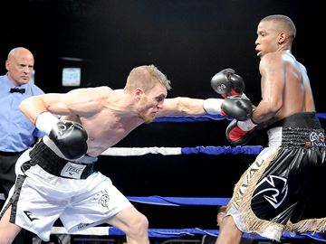 Oakville resident Ryan Young (white trunks) delivers a blow to Montreal's Mitch Louis-Charles during a United Boxing Promotions event Saturday at Mississauga's Hershey Centre. Young won the battle of middleweights by technical knockout as Louis-Charles was unable to answer the bell for the fourth round due to injury, and is now 2-0 in his UBP career.