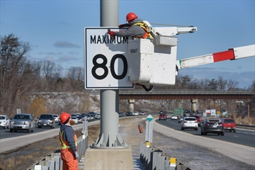 Workers from the City of Hamilton install one of the new 80 km/hr signs along the Red Hill Valley Parkway between Greenhill Avenue and the QEW in Hamilton on February 16, 2019.