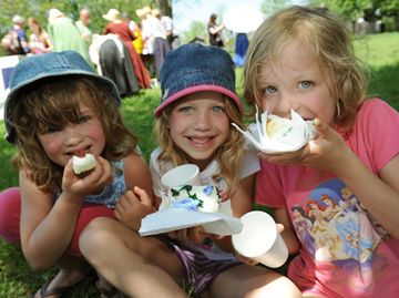 Sisters Amy, Julia and Charlotte enjoy birthday cake in the town square.