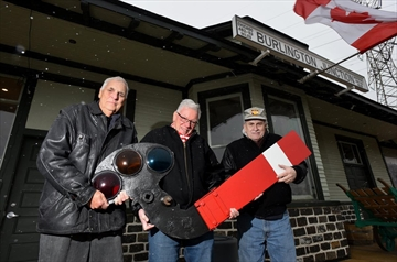 Brian Aasgaard, left, Ron Danielson, centre, and John Mellow, holding a train order signal, have been the driving force behind the renovation of the Freeman Station in Burlington.