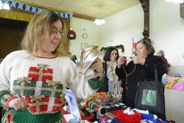 The Weston Craft Guild's Sandra Fioroni, left, displays some of the group's work, including her sweater, while shoppers browse the items on the table during the Mount Dennis Legion Craft Fair on Saturday morning. (Dec. 7, 2013)