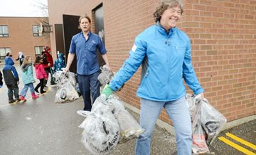 Vaughan regional councillor Deb Schultz helps school custodian Frank McDougall carry the bags to the dumpster after a 20-minute clean-up outside at Glen Shields Public School in Thornhill on Friday afternoon April 19.