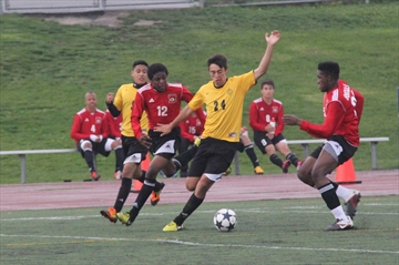 The St. Marcellinus Spirit hosted their fifth annual Friday Night Lights soccer triple header last night. The Spirit's Daniel Buckley (right) and Jessie Bibby (12) close in on Miguel Gaitan of the Philip Pocock Pirates in the junior boys' contest.