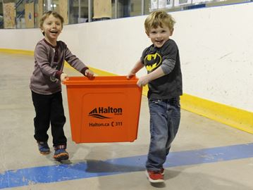 Colton Woolfenden, 4, (left) and buddy Jack Patrick, 4, team up to carry their Household Hazardous Waste Orange Box, around the arena floor.
