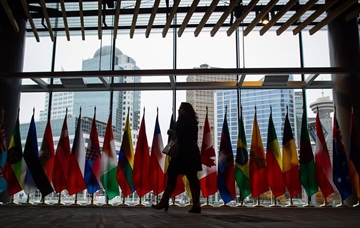 A woman walks past the flags of participating nations at the 2017 United Nations Peacekeeping Defence Ministerial conference in Vancouver, B.C., on Tuesday November 14, 2017. The two-day conference is largest gathering of defence ministers dedicated to UN peacekeeping. THE CANADIAN PRESS/Darryl Dyck