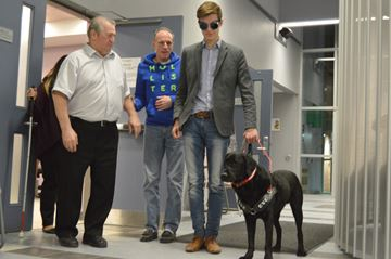 Sam Oosterhoff walks down the front lobby of the West Lincoln municipal buildings wearing blind goggles, holding Keegan, Stephen Barker's guide dog.