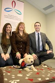 Hope, the puppy, has been donated by the Human Services and Justice System Coordination Committee to become an autism service dog. Pictured here with 9-week-old Hope is Seline Desnoyers of Autism Dog Services and Terri Dodgson and Michael Dunn of the Human Services and Justice System Coordination Committee.