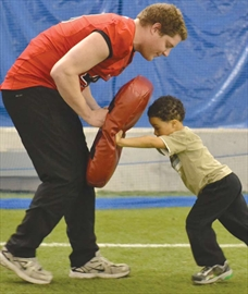 Dylon Mitchell, 4, works on his football skills with Carleton Ravens' player Connor Picco. The last session of the Be a Bengal not a Bully program ran on March 29 at the Hornet's Nest. The Orléans Bengals Football Club partnered with the Carleton University team to run a special skills session to finish winter training.