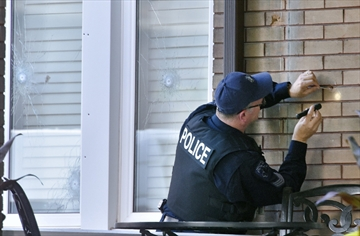 A Hamilton police officer collects bullets from the brick on the front of Pat Musitano's home on St. Clair Boulevard.