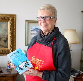 Elinor Montgomery wears one of the aprons and holds a very special book that are part of the first even Canadian Heritage Christmas in Kingston.