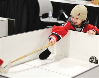 Tyler Finn, 2, is all smiles as he plays mini-sticks with his big brother at Hockeyfest, held Nov. 24 at the Ernst and Young Centre. The two-day event was held for the first time this year and featured games, vendors, and speakers. For more photos, see page 17.