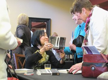 Guest speaker Kim Phuc signs copies of her book at the 11th annual Whitchurch-Stouffville Prayer Breakfast at Station Creek Golf Club in Gormley May 16.