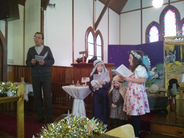 The Reverend Michael Marshall with Marie Penfold playing Mary, with her sister Holly playing Joseph and her sister Aimee playing the Angel at the Florence Universal Church on Sunday, Dec. 4.