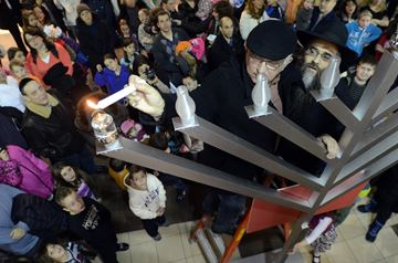 Favel Hecht lights the first candle of the menorah with help of Rabbi Chaim Hildeshaim at Chanukah celebrations at the North Thornhill Community Centre on Wednesday evening November 27.