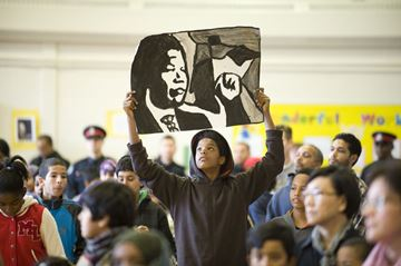 Basboos Zein holds up a drawing during the memorial service for Nelson Mandela at Regent Park's Nelson Mandela Park Public School Friday.