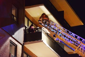 Firefighters use a ladder to reach residents in an apartment blaze early Saturday morning at 455 Maple Ave. in Burlington