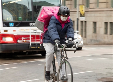 A Foodora delivery courier wears a face mask as a precautionary measure en route near Front and Yonge Street.