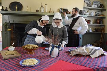 Sarah Fairley, left, Claire Ricci and Michael Shelbourn prepare for tea time during National Tartan Day activities at the Gibson House Museum on Sunday.