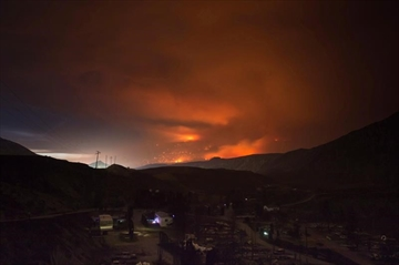 A wildfire burns on a mountain in the distance east of Cache Creek behind a trailer park that was almost completely destroyed by wildfire, in Boston Flats, B.C., in the early morning hours of July 10, 2017. Federal officials visiting wildfire-affected communities in British Columbia are expected to give an update today on the state of the response. Members of a federal ad hoc committee leading the government's fire response, including Public Safety Minister Ralph Goodale and Defence Minister Harjit Sajjan, will be meeting with provincial officials in Prince George this morning. THE CANADIAN PRESS/Darryl Dyck